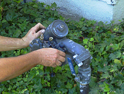 an irrigation repair specialist is doing a backflow repair